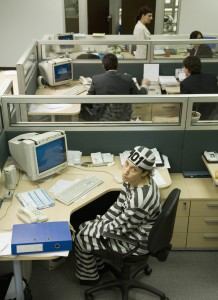 Businesswoman at desk in convict's outfit